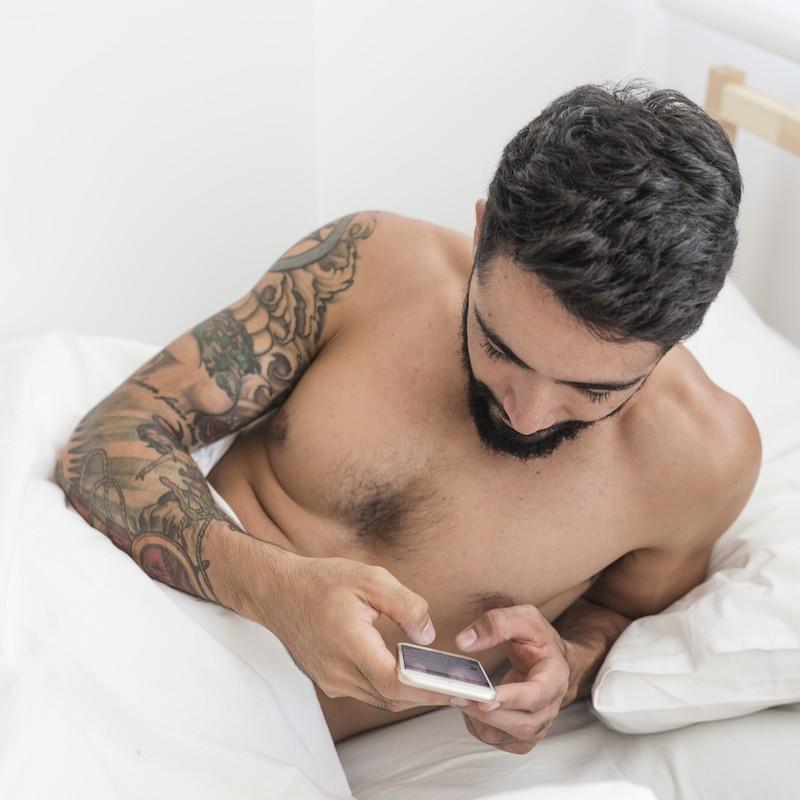 homme au lit avec téléphone portable