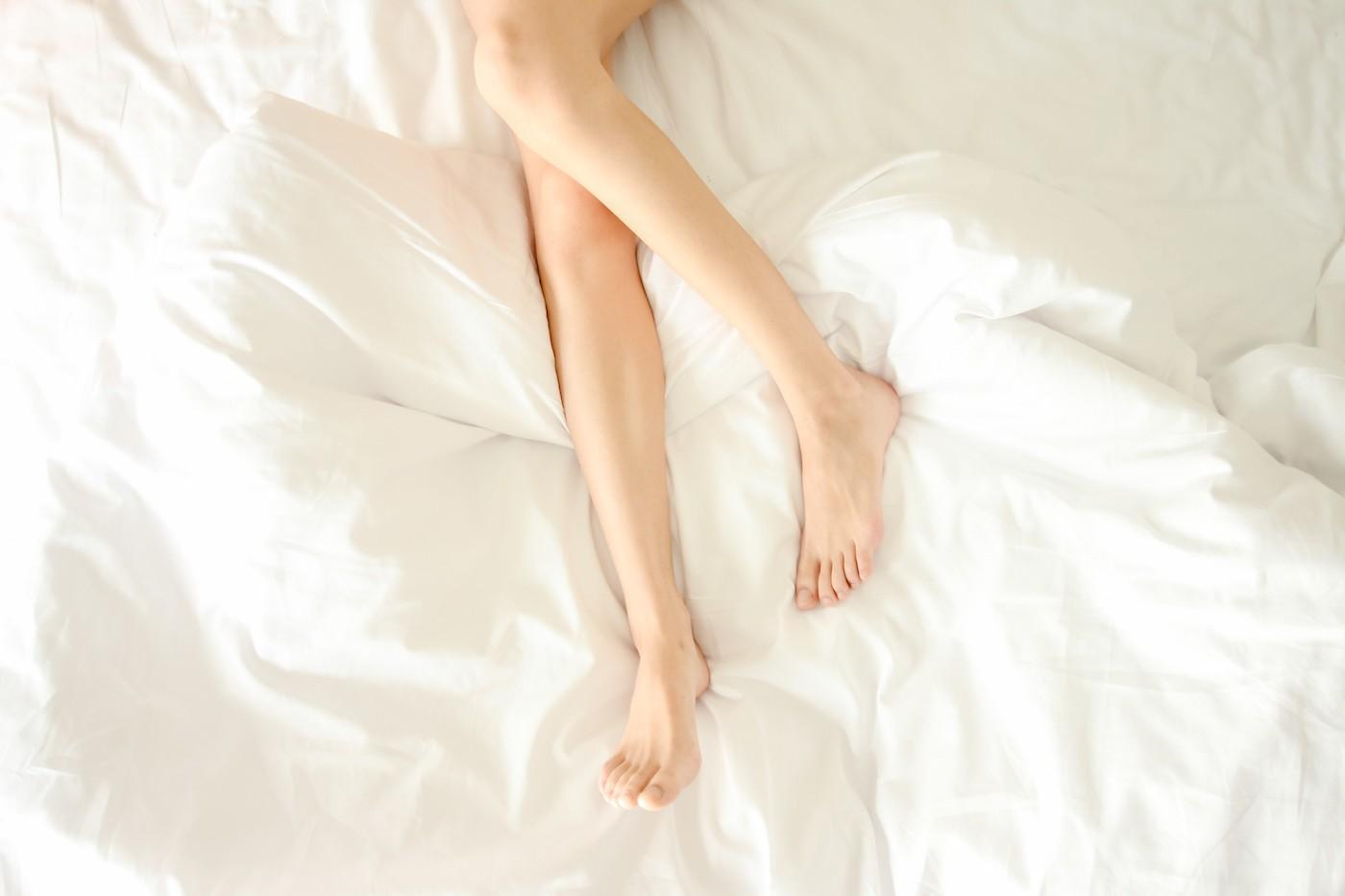 Piernas de mujer sobre cama